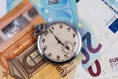 Zeit ist Geld Konzept; Eurobanknoten mit Weinlesetaschenuhr stockfotos
