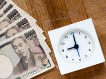 Zeit ist Geld Uhr und Japaner 10000 Yenrechnungen auf dem hölzernen Stockbilder