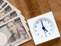 Zeit ist Geld Uhr und Japaner 10000 Yenrechnungen auf dem hölzernen Stockfotos