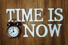 Zeit ist jetzt Alphabetbuchstabe mit Wecker auf h?lzernem Hintergrund stockfoto