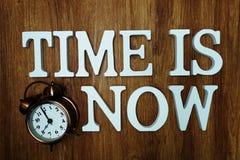Zeit ist jetzt Alphabetbuchstabe mit Wecker auf h?lzernem Hintergrund lizenzfreie stockfotografie