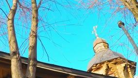 Zeit 4K hüllt hölzerne Kirche der Hauben mit einem goldenen Kreuz gegen den Himmel mit Wolken ein stock video