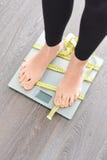 Zeit, Kilogramm mit den Frauenfüßen zu verlieren, die auf eine Gewichtsskala treten Lizenzfreie Stockfotografie