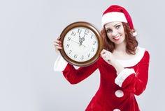Zeit-Konzept und Ideen Vergnügte rothaarige Santa Helper With Big Round-Uhr und darstellen Zeit Stockfotos