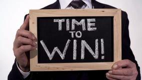 Zeit, Motivationsphrase auf Tafel in den Geschäftsmannhänden, Inspiration zu gewinnen stockfotografie