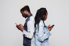 Zeit, Telefone zu benutzen Seitenporträt von den afrikanischen Paaren, die zurück zu der Rückseite hält Handys gegen weißen Hinte stockfoto