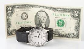 Zeit und Geld - übergeben Sie Uhr mit 2 Dollar Stockfotos