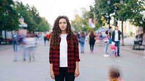 Zeit-Versehen des einsamen Mädchens stehend im Stadtzentrum auf dem Bürgersteig, der tragende Freizeitbekleidung der Kamera wenn  stock video