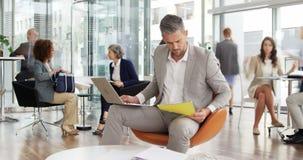 Zeit-Versehen des Geschäftsmannes sprechend am Handy bei der Anwendung des Laptops