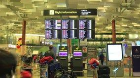 Zeit-Versehen: Internationaler Flughafen Singapurs, Changi, Besucher, die Abfahrtstafel betrachten