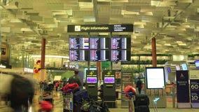Zeit-Versehen 4K: Internationaler Flughafen Singapurs, Changi, Besucher, die Abfahrtstafel betrachten stock video