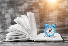 Zeit zu lesen Buch und Weinlesewecker auf dem Holztisch Lizenzfreie Stockfotos