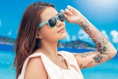 Zeit zu reisen Mädchen in der Sonnenbrille, die auf dem Seehintergrund betrachtet frohe Nahaufnahme der Sonne lokalisiert steht stockbilder
