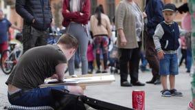Zeitgenössische Kunst, behinderter Mann schafft Malereien und großzügige Passanten werfen Geld in Glas am Marktplatz stock video footage