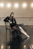 Zeitgenössischer Balletttänzer auf einem Holzstuhl auf einer Wiederholung lizenzfreie stockfotografie