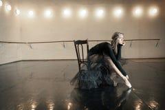 Zeitgenössischer Balletttänzer auf einem Holzstuhl auf einer Wiederholung stockfoto