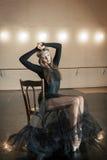Zeitgenössischer Balletttänzer auf einem Holzstuhl auf einer Wiederholung lizenzfreies stockbild