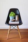 Zeitgenössischer schwarzer speisender Stuhl mit Betriebsbüchern und -kerzen stockbild