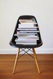 Zeitgenössischer schwarzer speisender Stuhl mit Stapel Büchern stockfotografie