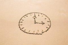 Zeitkonzept - Bild eines Ziffernblattes auf sandigem Strand Lizenzfreies Stockfoto