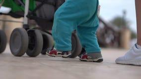 Zeitlupe - Beine des Kleinkindes und der Mutter nahe Spaziergänger stock footage