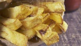Zeitlupe besprühen Salz auf gebratenen Kartoffeln nah oben stock video footage