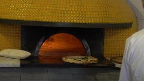 Zeitlupe-Chef, der italienische Pizza in traditionellen Holz-abgefeuerten Steinofen legt stock footage