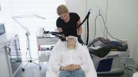 Zeitlupe Cosmetologist mit spezieller Ausr?stung tut Laser-Verfahren f?r Abbau von Blutgef??en auf dem Gesicht des M?dchens stock video footage