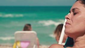 Zeitlupe der Frau Getränk auf einem schönen Strand durch Ozean genießend stock footage