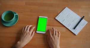 Zeitlupe der Hände der Frau, die Tabelle mit grünem Schirm Smartphone weitergehen stock video footage