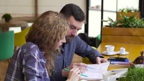 Zeitlupe der jungen Frau und jungen des Mannes, die zusammen ein Buch in einem Café liest stock video