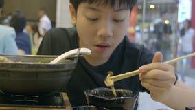 Zeitlupe des asiatischen netten Jungen genießen, japanisches Lebensmittel mit Lächelngesicht zu essen stock video footage
