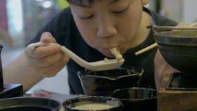 Zeitlupe des asiatischen netten Jungen genießen, japanisches Lebensmittel mit Lächelngesicht zu essen stock footage