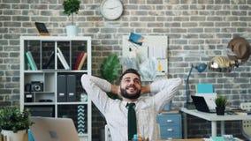 Zeitlupe des Bargeldes fallend auf den aufgeregten Unternehmer, der bei Tisch im Büro sitzt stock footage