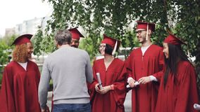 Zeitlupe des Collegelehrers seine Studenten umarmend und Hände am Graduierungstag mit Freude und Stolz rüttelnd Grüne Bäume stock video
