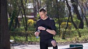 Zeitlupe des erschöpften Trinkwassers des Rüttlers von der Flasche nach der Fertigung seines Trainings in einem Park stock video