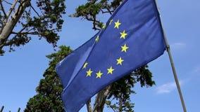 Zeitlupe des Europäers fahnenschwenkend im Wind auf Fahnenmast an Europa-Stadt stock footage
