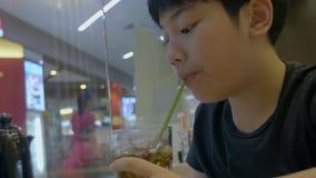 Zeitlupe des Jugendlichen ein Glas Auffrischung des kalten sprudelnden Cola mit Lächelngesicht trinkend stock video footage