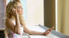 Zeitlupe des jungen blonden Mädchens im Kleid ist hörende Musik durch ihren Smartphone am Kaffeestubecafé stock footage
