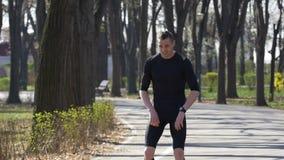Zeitlupe des sportiven anziehenden Atems des Jungesitzes nachdem dem Rütteln in einem Park stock video