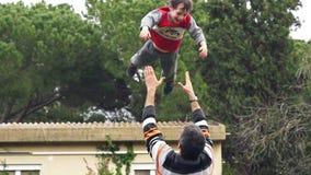 Zeitlupe des Vaters seinen entzückenden Sohn in der Luft werfend stock video footage