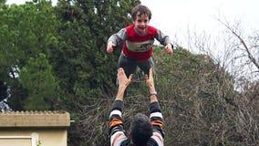 Zeitlupe des Vaters seinen entzückenden Sohn in der Luft werfend stock footage