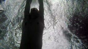 Zeitlupe, die Ansicht von unten über den jungen Sport bemannen das Schwimmen in den Poolschmetterlingsanschlag vor dem hintergrun stock footage