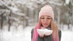 Zeitlupe, eine Frau in einem Jackenhut und Schal im Winter im Forstbetriebschnee in ihren Händen und Schlag in stock video
