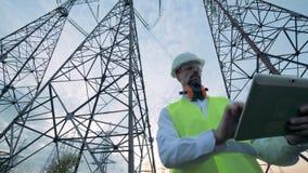 Zeitlupe eines männlichen Ingenieurs, der mit einer Tablette nahe Stromleitungen arbeitet stock video footage