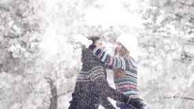 Zeitlupe: glückliches Paar, das mit Schnee im feenhaften Winterwald spielt stock footage