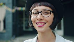Zeitlupe Headshot der schönen jungen Frau im Hut und in den Gläsern draußen stock video