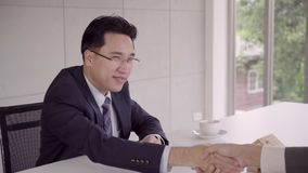 Zeitlupe - intelligente hübsche Geschäftsmänner, die Hände rütteln, nachdem ein Hausvertrag, eine Einstellung und ein Vereinbarun stock video footage