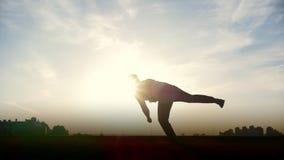 Zeitlupe - junger männlicher Parkour-tricker Pullover führt überraschende leichte Schläge vor der Sonne durch stock footage