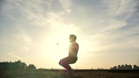 Zeitlupe - junger männlicher Parkour-tricker Pullover führt überraschende leichte Schläge vor der Sonne durch stock video